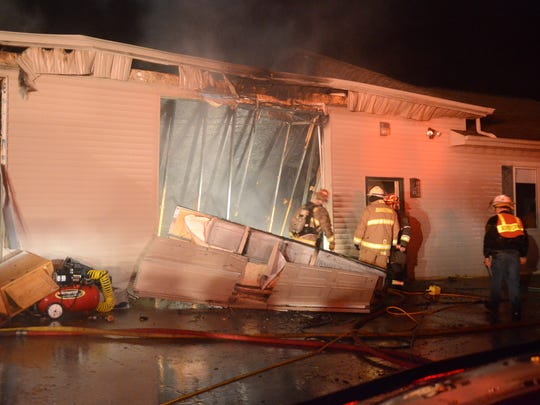 Fire early Sunday heavily damaged a garage and storage building and caused some damage to the attached home.