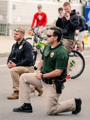 Seabrook Deputy Police Chief Kevin Gelineau, left, and Lt. Alex Reno of the Hampton Police Department take a knee in solidarity during a rally Monday at Hampton Beach to protest the killing of George Floyd.