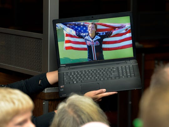 Family members watch Olympic BMX racer Alise Post draped
