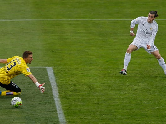 Real Madrid's Gareth Bale, right, scores his side's third goal past Getafe's goalKeeper Vicente Guaita during a Spanish La Liga soccer match between Real Madrid and Getafe at the Alfonso Perez stadium in Getafe, near Madrid, Saturday, April 16, 2016. (AP Photo/Francisco Seco)