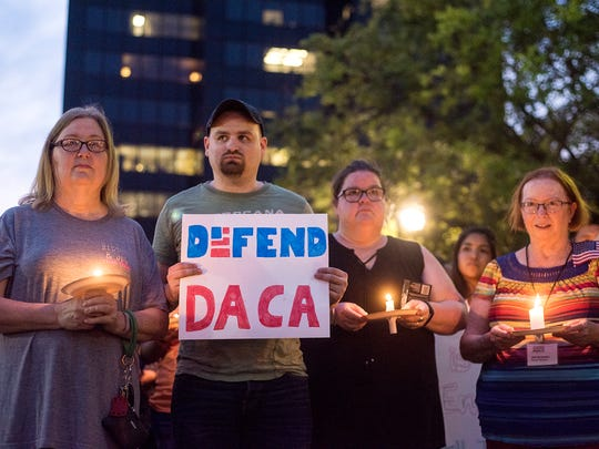Martha Waggonner, Walker Waggonner, Katie Powell and Gail McGlothin stand in silence holding candles and signs during a silent vigil in honor of Deferred Action for Childhood Arrivals (DACA) at T.B. Butler Fountain Plaza in Tyler, Texas, on Tuesday, Sept. 5, 2017. Nearly 500 people attended the vigil on the day that the Trump administration announced that they would phase out the program.