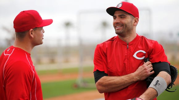 Reds first baseman Joey Votto (right) jokes with catcher