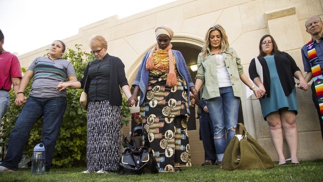 Salama Lupandu (center), a former refugee from the Republic of Congo, holds hands while the group prays during an interfaith gathering showing support for refugees at Grace Lutheran Church on Feb. 2, 2017, in Phoenix.