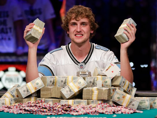 Ryan Riess holds up two bricks of $100 bills after