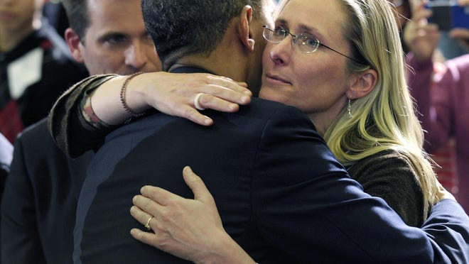 FILE - In this April 8, 2013, file photo, President Barack Obama embraces Scarlett Lewis, mother of Sandy Hook Elementary School shooting victim Jesse Lewis, after speaking at in Hartford, Conn. Through his death in a gun battle with police on Sunday, June 12, 2016, the Orlando nightclub gunman deprived his victims' families of the chance for a trial that could have helped to channel grief, offer a sense of justice or provide answers for the bloodshed. In Newtown, Conn., where the gunman took his own life after killing 26 people inside the school in December 2012, Lewis said his survival only would have made it more difficult as she grieved for her murdered son, Jesse.
