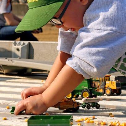 Laramie Massie, 2, of Coshocton, plays with farm machinery