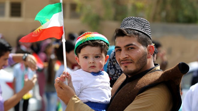 An Iraqi Kurdish man poses as he carries a child wearing the Kurdish flag on his head during a celebration in the northern city of Kirkuk on Sept. 25, 2017.