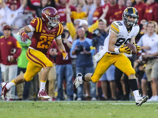 Iowa's Matt VandeBerg makes a 48-yard catch behind Iowa State's Darian Cotton to convert a third-and-21 in the fourth quarter of the Hawkeyes' 31-17 win.