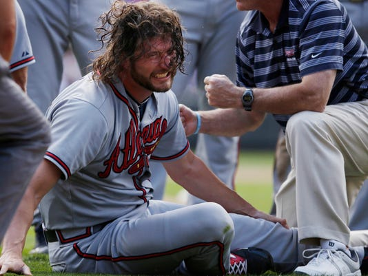 Atlanta Braves relief pitcher Jason Grilli reacts to an injury to his left leg while running to cover first base during the ninth inning of a baseball game against the Colorado Rockies in Denver on Saturday, July 11, 2015. Grilli left game and was taken from the field on a medical cart. (AP Photo/Joe Mahoney)