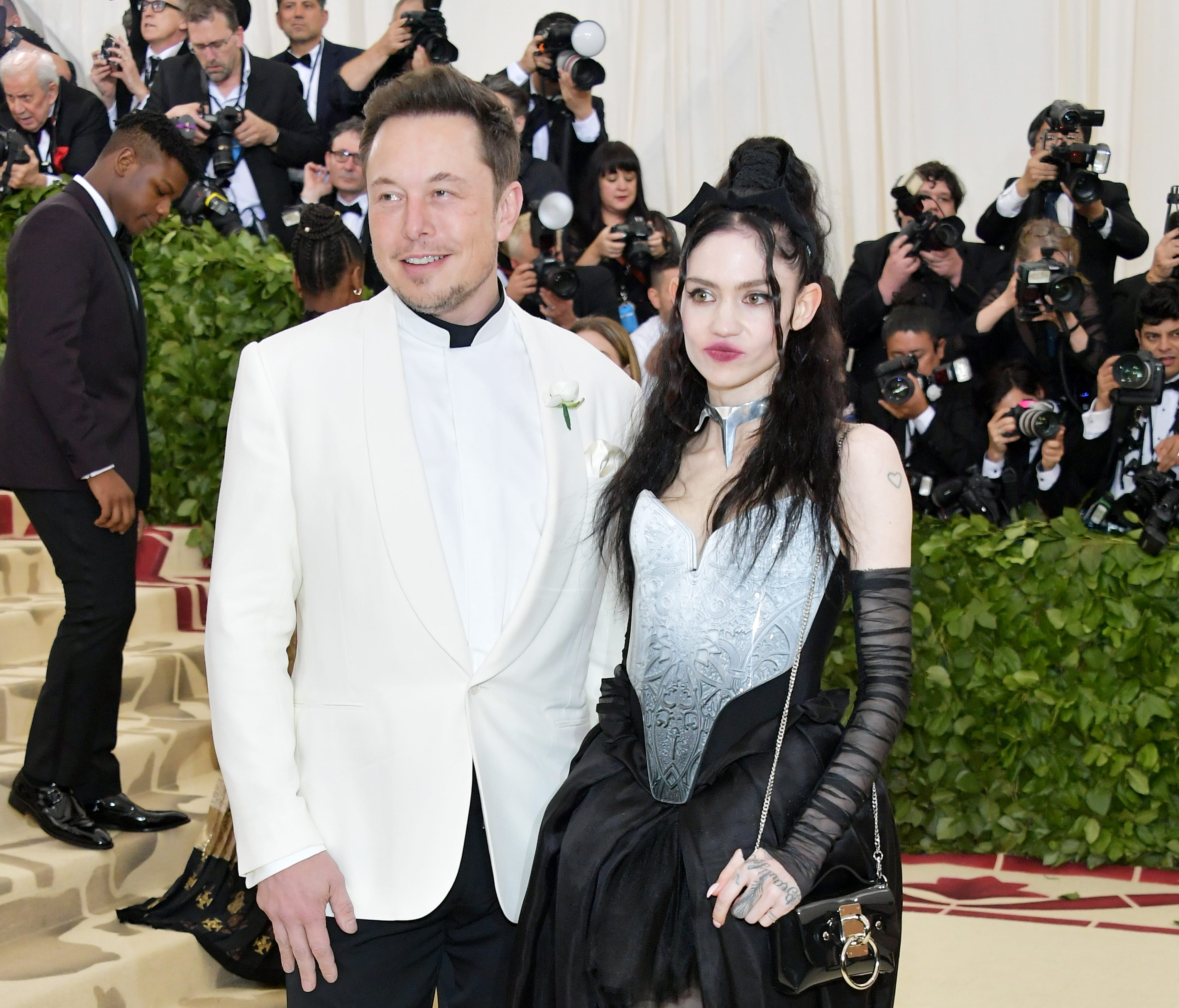 Elon Musk and Grimes arrive at the Met Gala together, making their relationship red-carpet official.