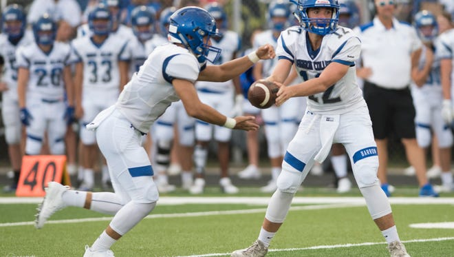 Barron Collier quarterback Jacob Kuhlman hands the ball off to running back Andres Satizabal during the game against Lely at Lely High Friday night, August 18, 2017.