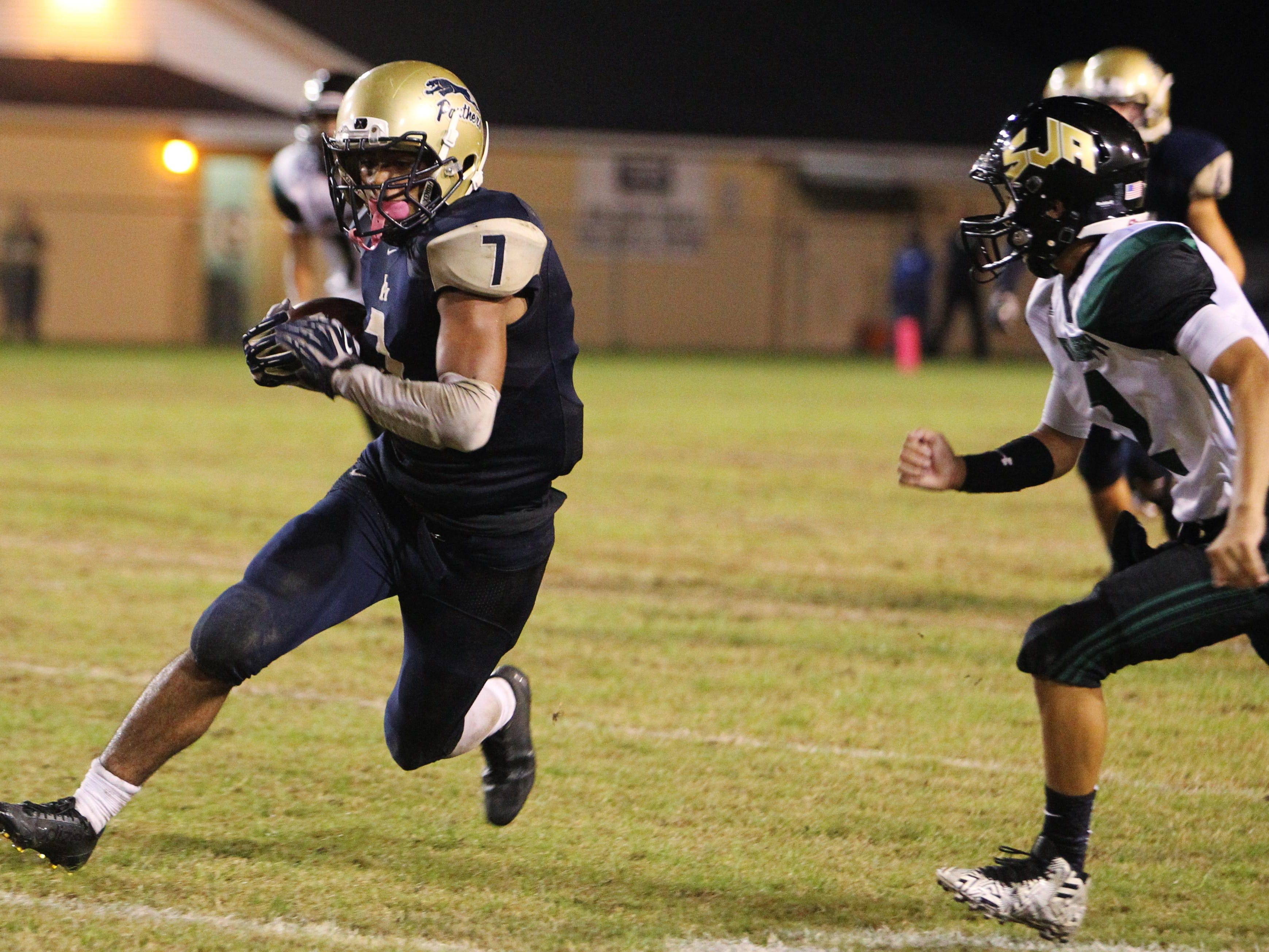 John Paul II's Sam Smith sprints away from defenders in the championship game of the North Florida Football Conference at Gene Cox Stadium.