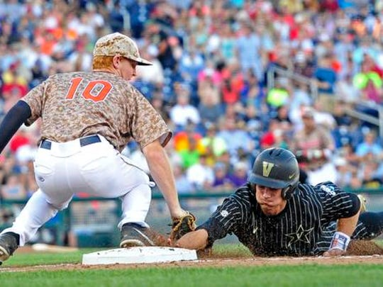 Virginia Pavin Smith (10) tags out Vanderbilt's Bryan Reynolds in a pickoff during the second inning in the College World Series at TD Ameritrade Park, Monday, June 22, 2015, in Omaha, Neb.