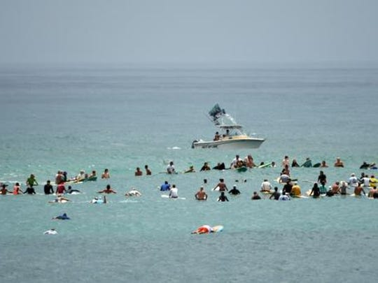 Hundreds turned out for Saturday's Paddle Out for legendary East Coast surfer Dick Catri at Sebastian Inlet.