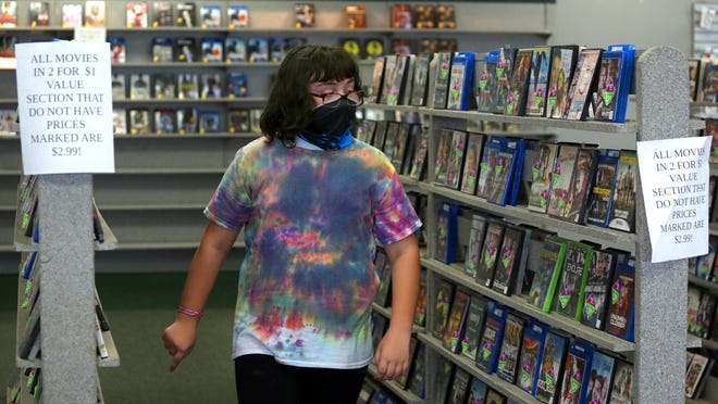 Zoe Melton, 11, walks through aisles of movies and games for sale at Family Video in Shelby on Monday. Melton's family visits the movie rental store every Friday night.