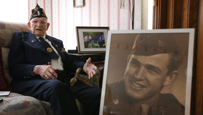 Ralph Osterhoudt at his home in Hyde Park on May 18, 2018. In the foreground is a portrait of Ralph taken while he was serving during WWII.