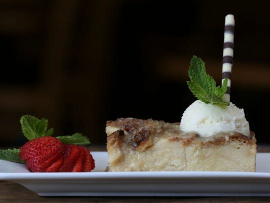 Bread pudding with bourbon sauce and a side of strawberries served at the Derby Cafe.