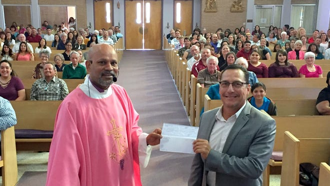 Father Ron Machado, standing at left, and Ray Trejo, board member for the Cancer Support of Deming and Luna County Inc. were at Sunday service at Holy Family Catholic Church for a special presentation. Fr. Ron handed a check to Trejo in the amount of $2,269 for the Celebration of Life Cancer Walk hosted by the support group in May. Fr. Ron told the congregation they were responsible for the donation through their gracious support of Holy Family fund-raising events. the Celebration of Life Cancer Walk raises tens of thousands of dollars annually in support of cancer patients in Deming and Luna County. This year will mark the 12th annual walk.