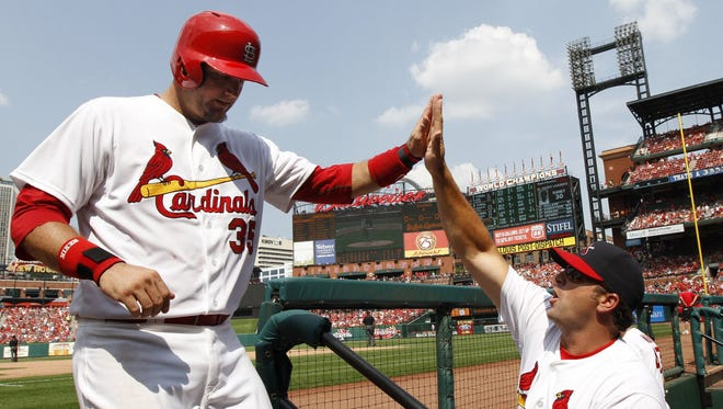 St. Louis Cardinals' A.J. Pierzynski is congratulated by manager Mike Matheny as he returns to the dugout after tying the game with a single against the Milwaukee Brewers during the seventh inning on Sunday, Aug. 3, 2014, at Busch Stadium in St. Louis, Mo.