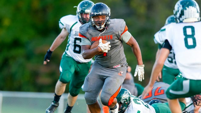 Beech Grove High School senior Brandon Bailey (1) breaks free of a tackle at the line of scrimmage and rushes the ball into the Monrovia secondary during the first half of action. Beech Grove High School hosted Monrovia High School in varsity football action, Friday, September 26, 2014.