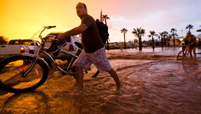 Pleasant Acres RV Park resident Michael Gill walks his bike across monsoon flood waters in Apache Junction, Ariz., on Aug. 30, 2013. An emergency alert went out to cellphones in the area warning of flash flooding.