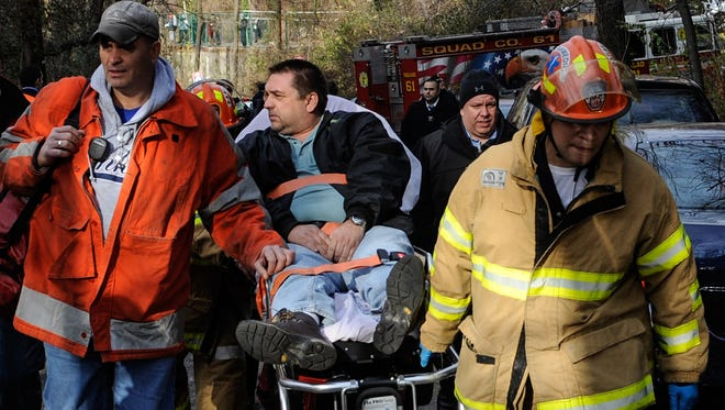 In this photo taken Sunday, Dec. 1, 2013, Metro-North Railroad engineer William Rockefeller is wheeled on a stretcher away from the area where the commuter train he was operating derailed in the Bronx, N.Y. The National Transportation Safety Board reported Monday, April 7, 2014, that the train Rockefeller was driving was going 82 mph around a 30-mph curve when it derailed killing four people and injuring more than 60.