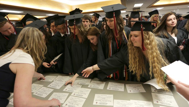 Graduates reach for their diplomas Sunday, May 25, 2014, after the SPASH graduation ceremony at the school in Stevens Point, Wisconsin.