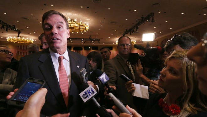 Sen. Mark Warner left, talks with members of the media after a debate with Republican Ed Gillespie at The Greenbrier in White Sulphur Springs, W.Va., on July 26, 2014.