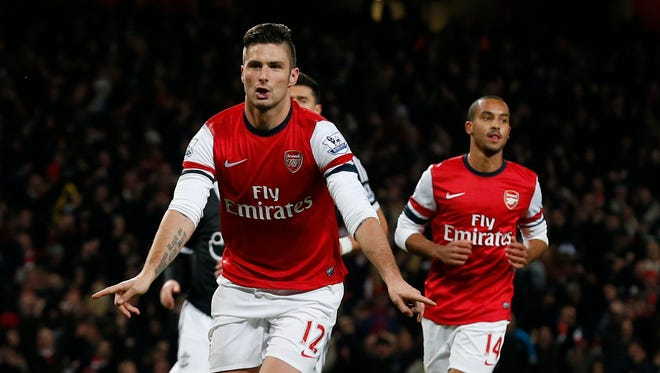Arsenal's Olivier Giroud, left, celebrates scoring a penalty and his second goal of the game beside Theo Walcott, right, during the English Premier League soccer match between Arsenal and Southampton at the Emirates Stadium in London, Saturday, Nov. 23, 2013.