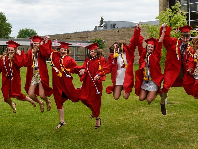 Graduates leap into the air during a group photo taken