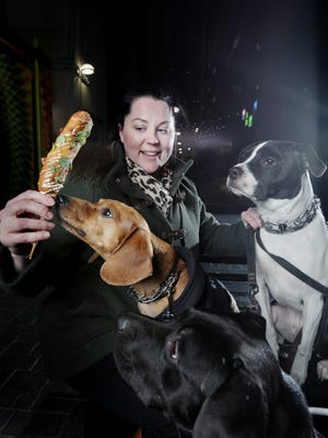 Standby chef Rebecca LaMalfa holds her Sonoran corn dog with her dogs Horton, Busby and Rooney at the Belt in downtown Detroit on Wednesday, Nov. 22, 2017.