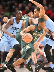 Michigan State guard Cassius Winston (5) dribbles around