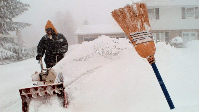 Dan Freitas tries to keep pace with the blowing snow as he attempts to clear his driveway in Penfield on March 4, 1999.