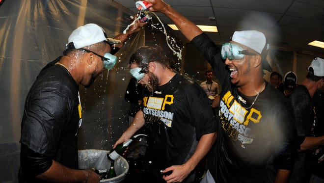 Pittsburgh pitchers Francisco Liriano, John Axford and Stolmy Pimentel celebrate in the clubhouse after clinching a playoff spot.