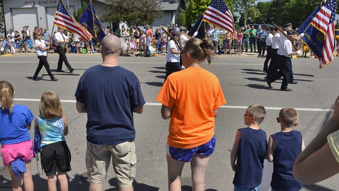 The crowd rises to its feet as the colors pass by to start the Bowlus Fun Day parade on July 6, 2014.