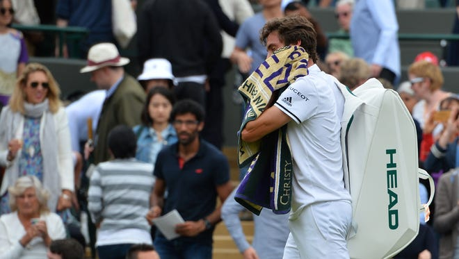 France's Gilles Simon leaves the court after being beaten by Bulgaria's Grigor Dimitrov during their men's singles second round match during Wimbledon Championships on June 30.