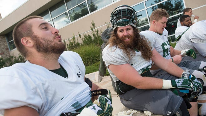 CSU offensive linemen Jake Bennett, left, and Fred Zerblis (long hair) joke around after practice Friday. They said they knew from a young age that offensive line was the position they were going to have to play in football.