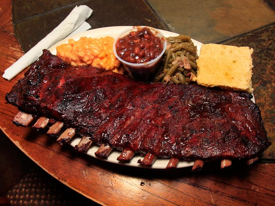 A slab of ribs with sides of mac and cheese, baked beans, green beans and cornbread, is one of the most popular meals on the menu at Barbecue and Bourbon on Main in  Speedway.