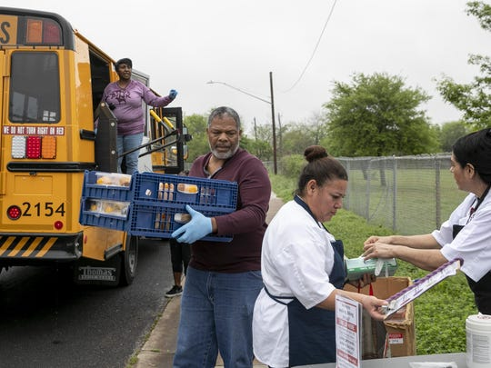 Austin school district bus driver Johnny McAfee unloads meals that he delivered on a school bus to Winn Elementary School on March 23. The district continued to provide free meals to its students and their parents amid the school closures caused by the coronavirus pandemic.