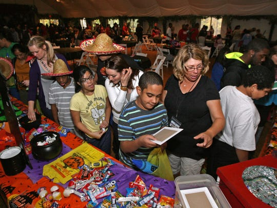 Juan Carlos, center, of Piscataway Regional Day School, visits the Halloween activity tables with teacher's aid Ellen Santoro. Students and teachers visit the Halloween tables at the party. The Greek hosts an annual Oktoberfest for the disabled community free of charge, at The Greek's Playland/Stone Museum, October 15 2014 Jamesburg NJ. Photo by Kathy Johnson BRI EST 1016 The Greek's Oktoberfest