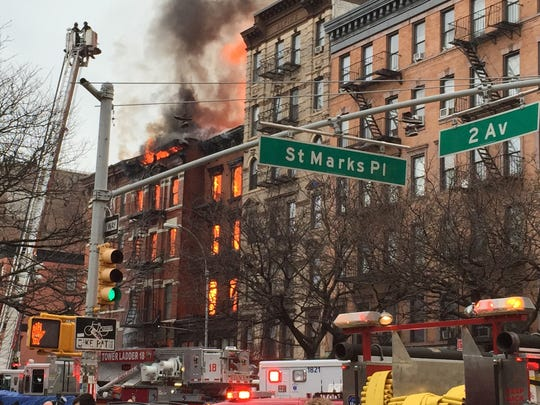 New York City firefighters work the scene of a large fire and a partial building collapse in the East Village neighborhood of New York on Thursday. Orange flames and black smoke are billowing from the facade and roof of the building near several New York University buildings.