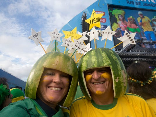 Brazil soccer fans wearing hats made of watermelons pose for a photo as they wait for the start of the World Cup soccer game between Brazil and Croatia inside the FIFA Fan fest area on Copacabana beach in Rio de Janeiro, Brazil, Thursday, June 12, 2014. The stars on the hat at left represent Brazil's previous five World Cup titles, and the other represents this year's possible sixth. (AP Photo/Silvia Izquierdo)