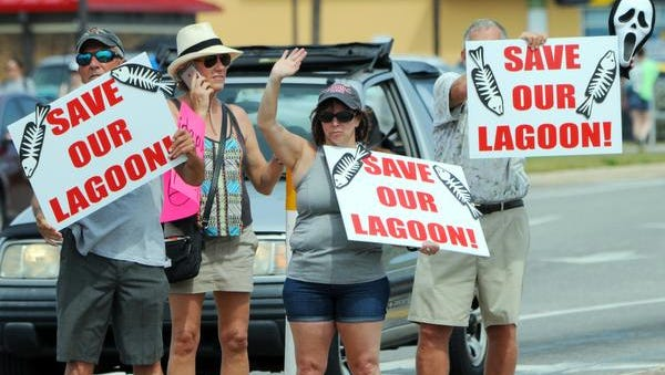 Citizens hold signs and seek support from drivers during today's rally for the Indian River Lagoon in Cocoa Beach.
