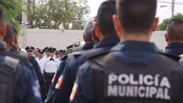 Juárez police officers stand at attention during a ceremony.