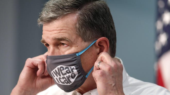Gov. Roy Cooper prepares to take off his mask to talk during a briefing at the Emergency Operations Center in Raleigh, N.C., Wednesday.