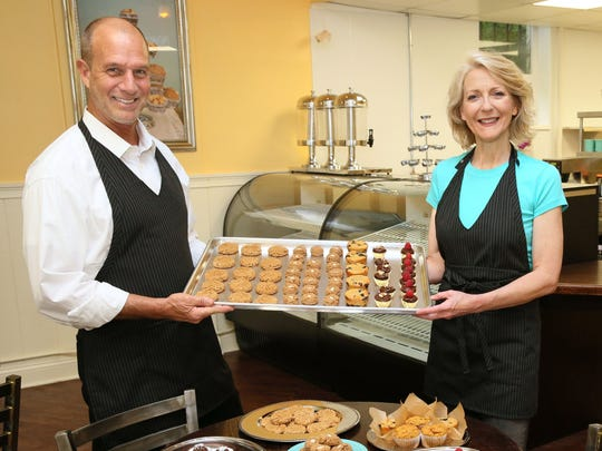 Susan Goulet and Lars Schloemer hold a selection of the gluten-free, grain-free, egg-free and dairy-free baked goods they create at Blooming Lotus Gourmet Bakery.