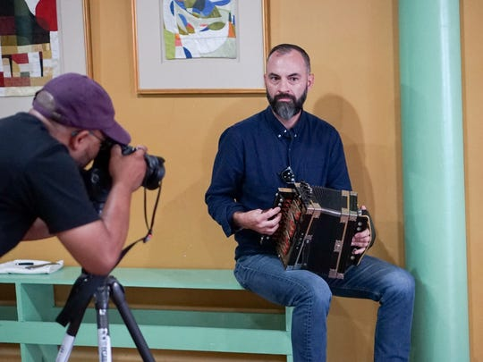 Roddie Romero plays music for couples during a dance lesson being recorded for an international marketing video.