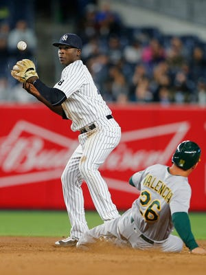 Yankees shortstop Didi Gregorius loses control of the ball as Danny Valencia of the Oakland Athletics slides in safely on a ball hit by Jed Lowrie during the fourth inning of a game at Yankee Stadium on Wednesday.