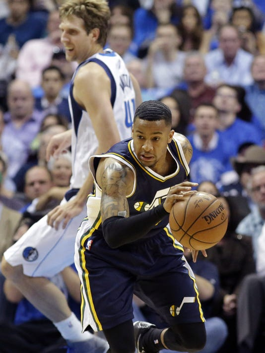 Utah Jazz guard Trey Burke, right, comes up with the steal against Dallas Mavericks forward Dirk Nowitzki (41) during the first half of an NBA basketball game, Thursday, Oct. 30, 2014, in Dallas. (AP Photo/LM Otero)