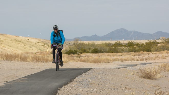 A bicyclist, rides toward Lohman Avenue on the newly built 3.2 mile trail running between Veternans Park and Sagecrest Park, stretching to Lohman Avenue, where the Las Cruces Dam over look is, December 8, 2016. Due to late summer storms parts of the trail are damaged and in need of repair.